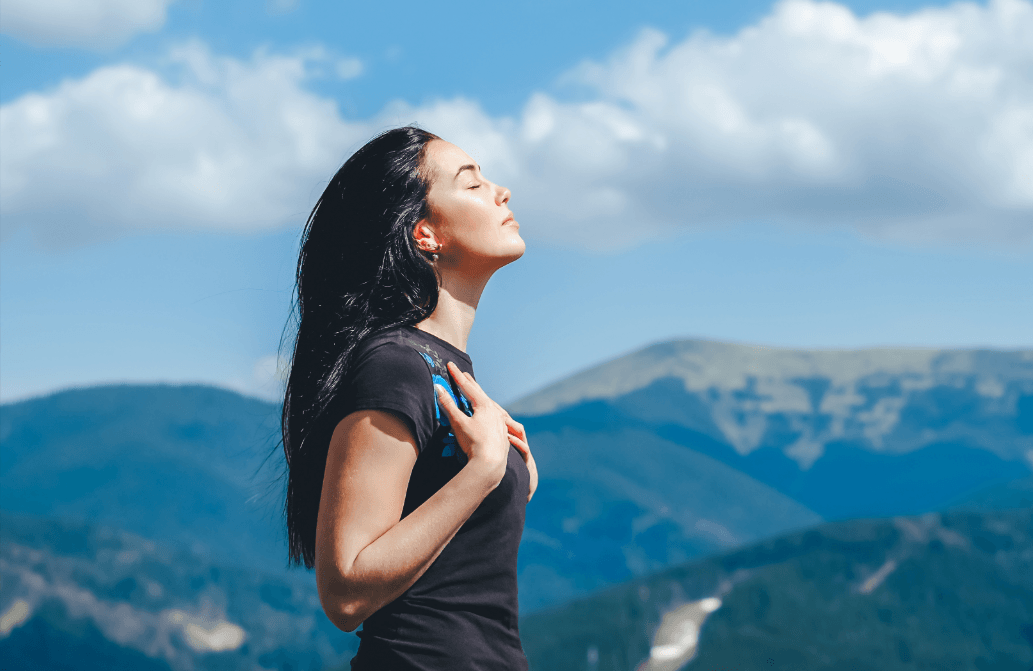 Long hair brunette girl on the top of the mountain enjoying fresh air.  Breathing.