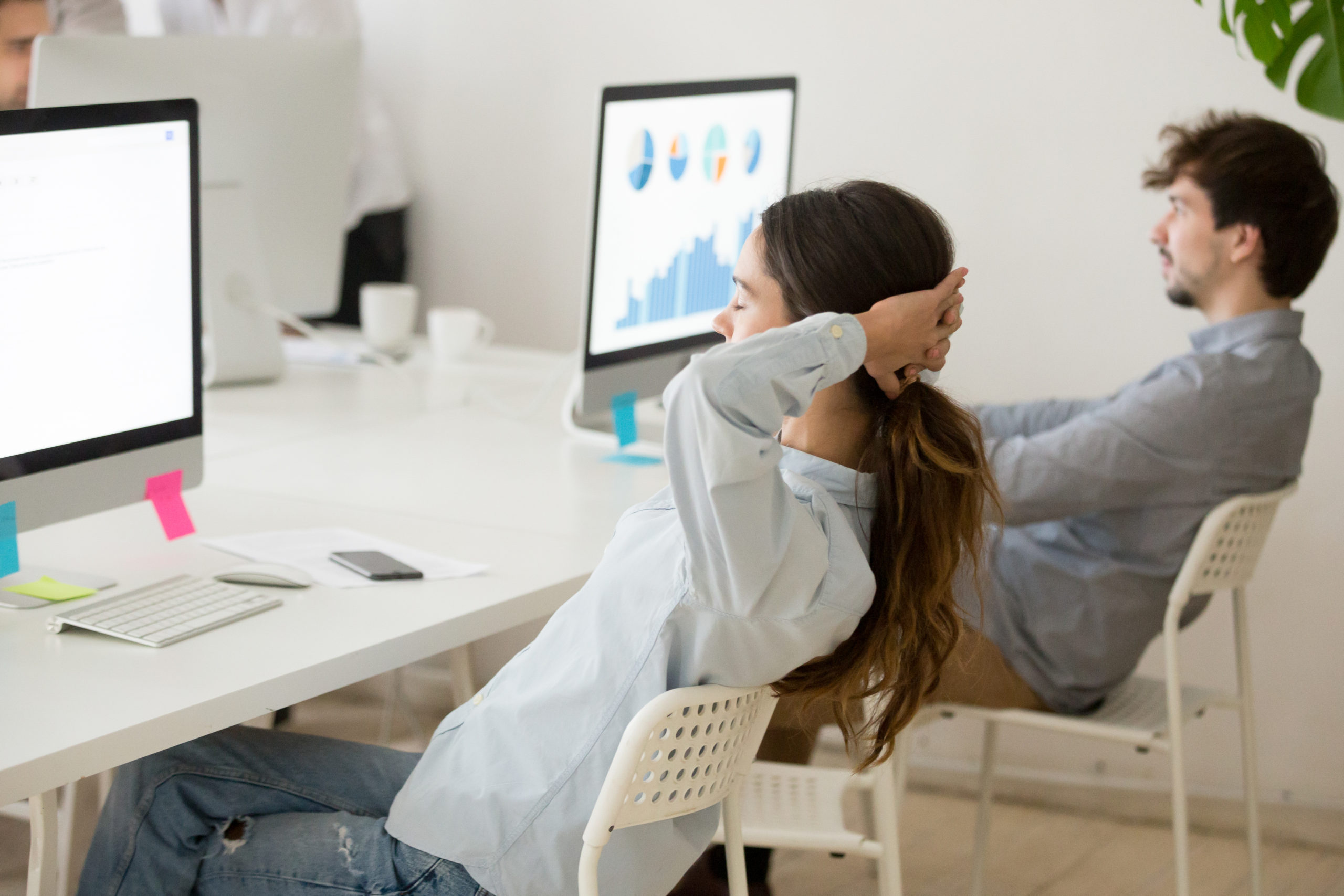 Female employee relaxing from computer work holding hands behind head. Forgetting about workplace stress